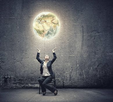 Image of businesswoman holding earth planet in hands above head. Elements of this image are furnished by NASA