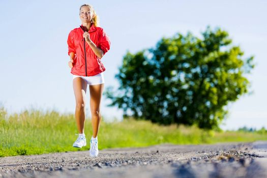 Image of young attractive woman running outdoor