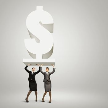 Image of two businesswomen holding dollar sign above head