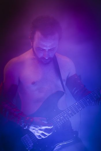 Rock star playing solo on guitar, neon lights