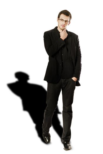 View of a young man standing against a white  background.