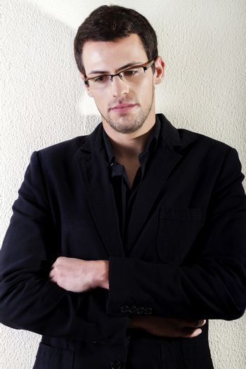 View of a young man standing against a white wall.