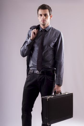 View of a young business man standing against a grey  background.