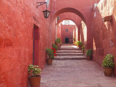 Red painted walls and arches design of alleyway through the Santa Catalina Monastery in Arequipa, Peru.