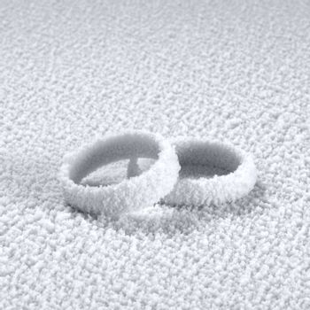 studio photography of two ice covered wedding rings in frosty back