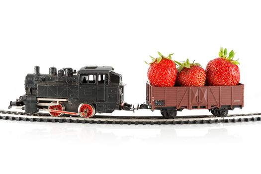 Toy train pulling carriage with strawberries