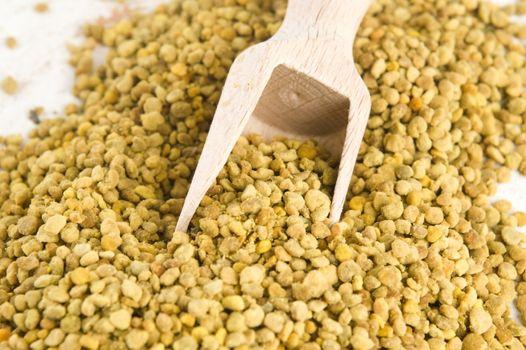 Bee pollen in wooden scoop. Nutritional supplement