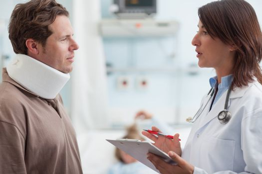 Doctor talking to a male patient with a collar on