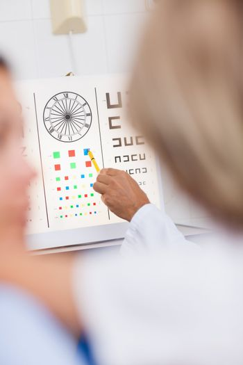 Eye test board being pointed at by a doctor in a hospital