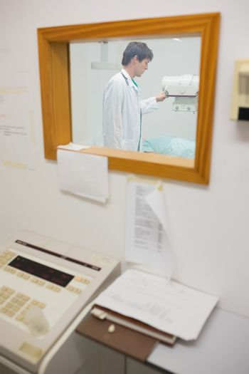 Sight of doctor doing a radiography through a window
