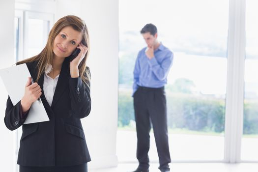 Woman calling on phone while man deciding