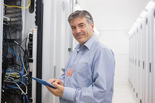 Smiling man doing maintenance on servers
