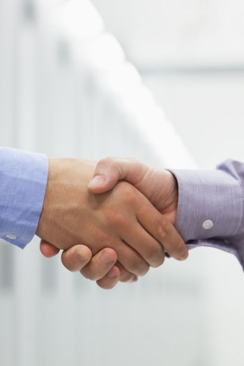 Two men shaking hands in hallway of data center