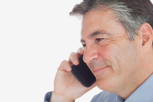 Mature businessman smiles while on call