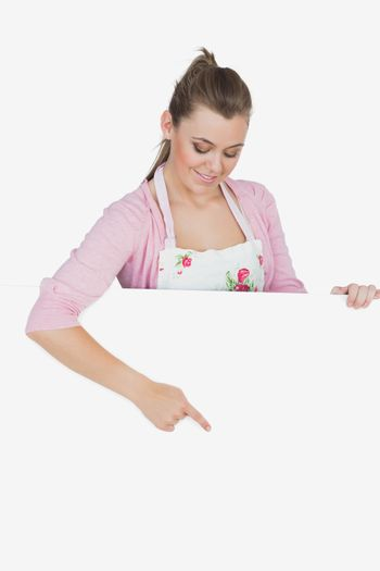 Maid in apron pointing at billboard