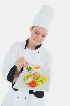 Chef seasoning dish with parsley