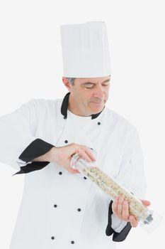 Mature chef using pepper mill