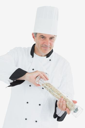 Confident chef using pepper mill