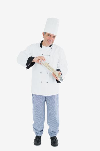 Happy chef using pepper mill