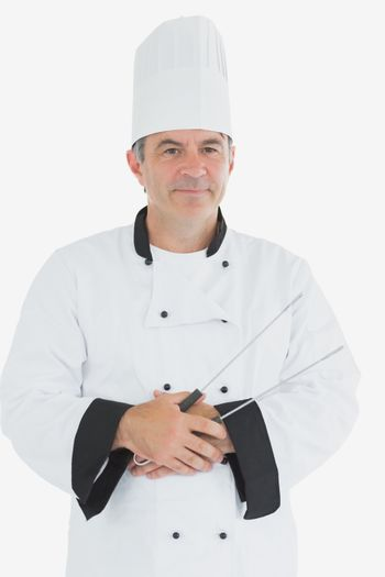 Mature chef holding tongs