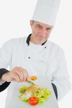 Chef garnishing prepared meal
