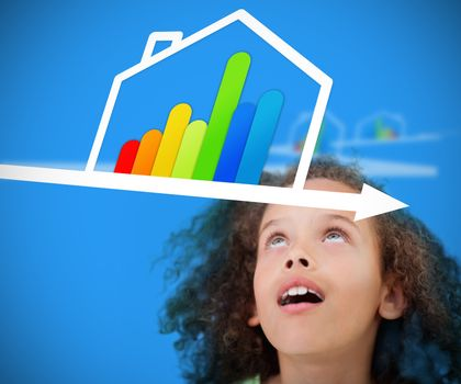Girl standing against a blue background looking at energy efficient house graphic