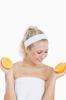 Happy woman looking at sliced orange