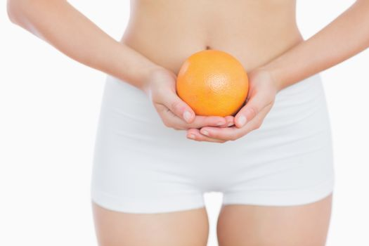 Fit woman holding fresh orange