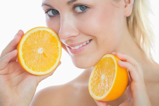Beautiful woman holding slices of orange