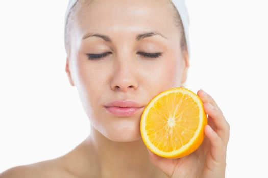Woman with eyes closed holding orange slice