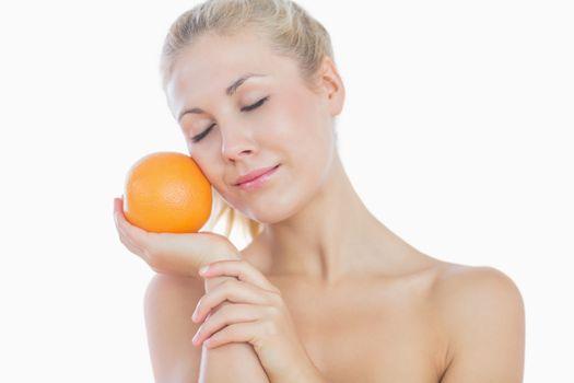 Topless woman holding orange