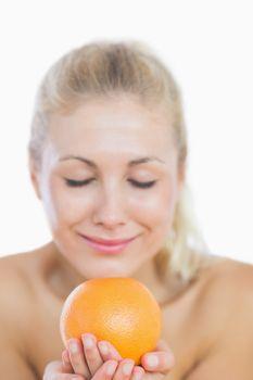Happy woman smelling fresh orange