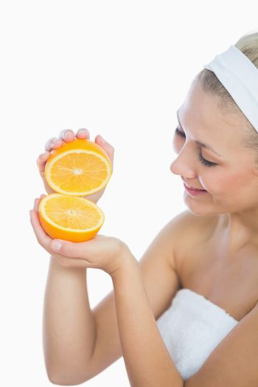 Happy woman holding slices of orange
