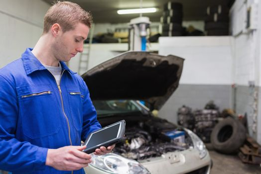 Mechanic with digital tablet at garage