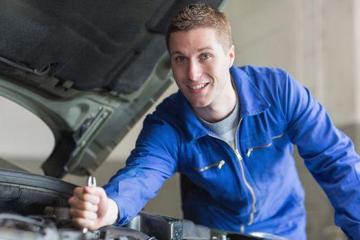Male mechanic working on automobile engine
