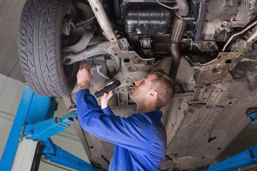 Repairman examining under car