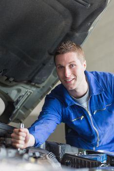 Auto mechanic working on motor