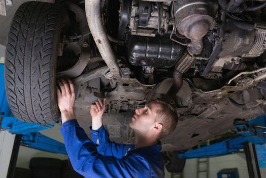 Mechanic under car in garage