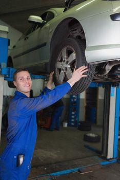 Car on hydraulic lift as mechanic examining tire