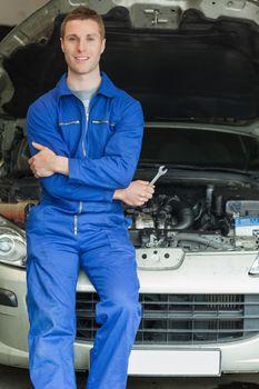 Happy mechanic leaning on breakdown car