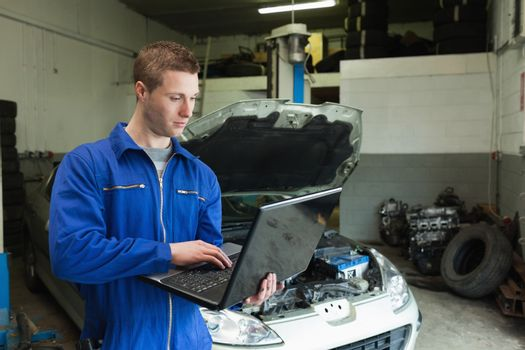 Mechanic using laptop in garage
