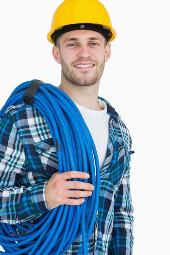 Portrait of smiling young male architect carrying coiled blue tubing