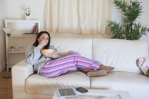 Relaxed woman sitting on couch with bowl at home