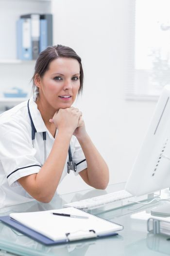 Nurse with hands under chin in front of computer at clinic