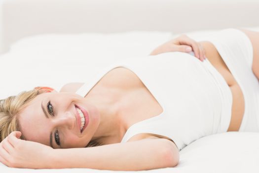 Portrait of smiling semi dressed woman lying in bed