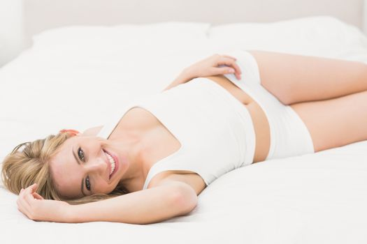 Smiling semi dressed woman lying in bed