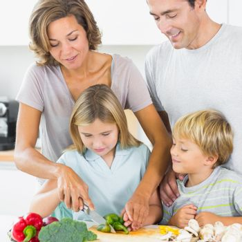 Mother teaching daughter to slice vegetables as father and son are watching in the kitchen