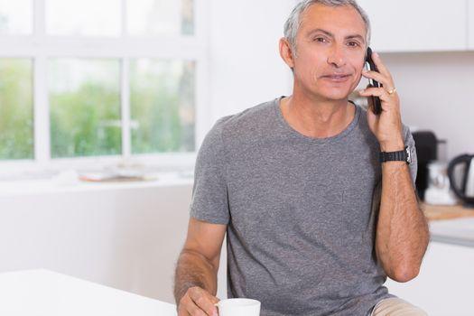 Man drinking while phoning
