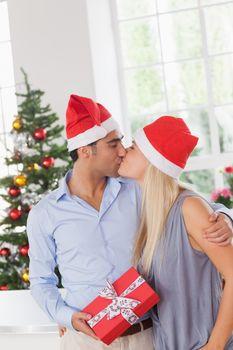 Kissing couple wearing santa hats at christmas