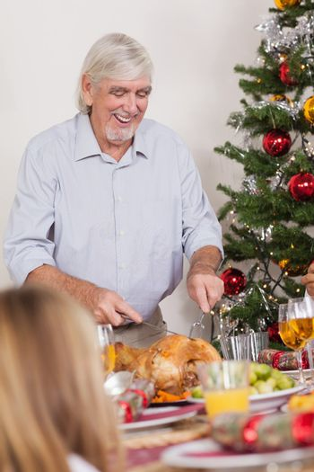 Grandfather carving christmas turkey